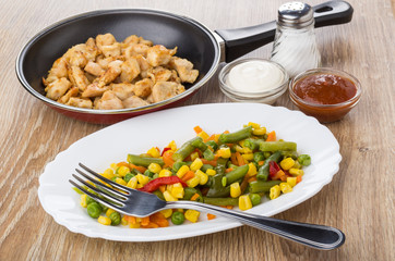 Vegetables in dish, fried meat, salt, bowls with sauces
