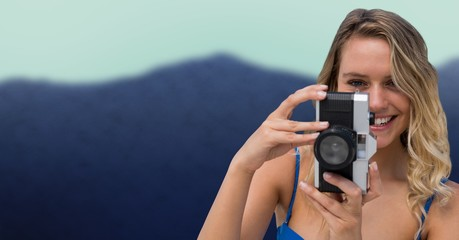 Close up of millennial woman with camera against blurry mountain