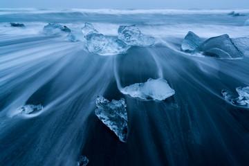Pezzi di ghiaccio sulla spiaggia nera nei pressi della baia di Jökulsárlón durante l'ora blu, Islanda