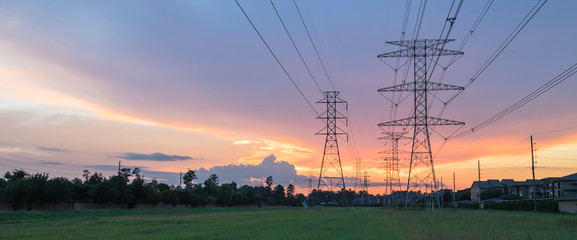 Group silhouette of transmission towers (power tower, electricity pylon, steel lattice tower) at twilight in US. Texture high voltage pillar, overhead power line, industrial background. Panorama style