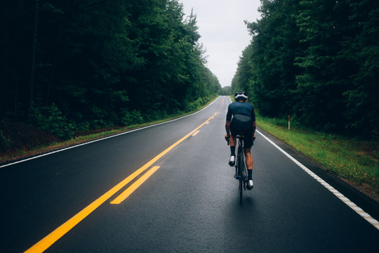 Selective focus shot of professional road cyclist riding down wet and windy mountain road in forest, on aero road bike from carbon