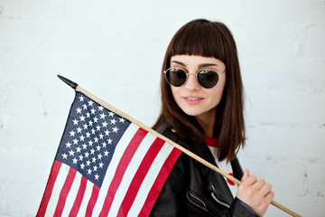 Sexy laughing female with round vintage glasses, millennial hipster outfit leather jacket holds little american flag, concept independence and freedom, stripes and stars