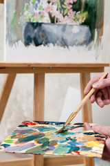 Artist paints a masterpiece. Palette of paint swatches with unfinished still-life painting on easel