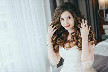 Luxury stylish bride sitting on the bed and looking at the camera