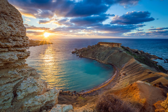Mgarr, Malta - Panorama of Gnejna bay, the most beautiful beach in Malta at sunset with beautiful colorful sky and golden rocks taken from Ta Lippija
