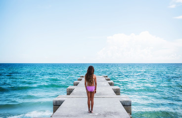 girl standing on pier looking at ocean