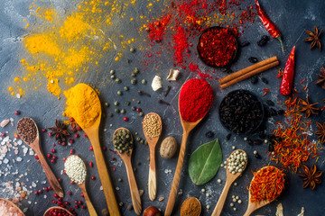 Various indian spices in wooden and silver spoons and metal bowls, seeds, herbs and nuts on dark stone table. Colorful spices, top view. Organic food, healthy lifestyle.