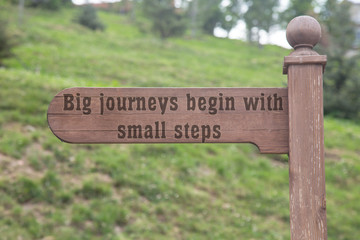 Big journeys begin with small steps text wooden sign with a forest background. wooden direction sign