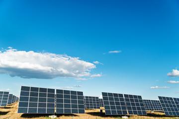Solar power plant under a blue cloudy sky