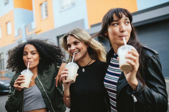 Three young females having ice coffee on city street