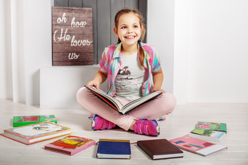 Happy child reads a book in the room. Schoolgirl. The concept of education and childhood.