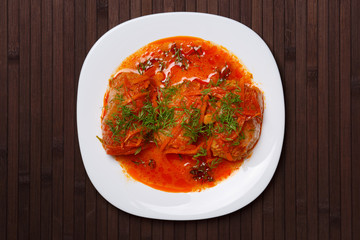 Cabbage rolls in tomato gravy on a white plate. Top view.