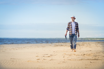 A man in smart casual hipster style with tablet combining work with relax on the beach of Baltic Sea