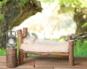 A newborn bed studio photography prop with a railroad lantern and a wooded forest background.  The bed is handmade from a Coral Bark Japanese Maple tree.