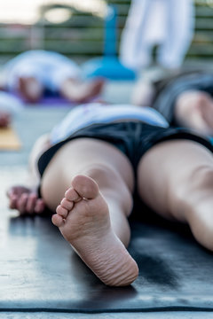 Woman lying in corpse pose relaxing after yoga class