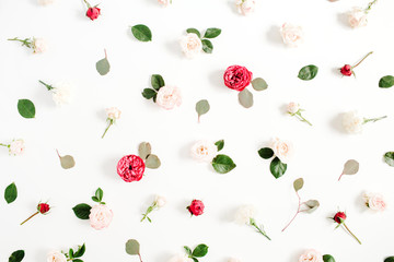 Floral pattern made of red and beige roses, green leaves, branches on white background. Flat lay, top view. Valentine's background. Pattern of flowers. Texture