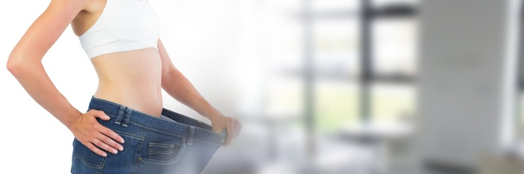 Slim healthy woman holding jeans fitting by window