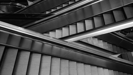 Modern interior design, modern escalators, chrome escalators. Black and White , monochrome, abstract artistic view. Modern art. Steel design. Architecture.