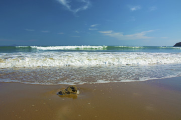 beautiful beach, on the sand roll frothy waves