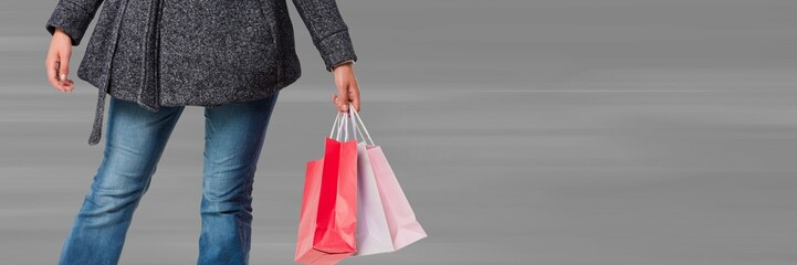 Shopper lower body with bags against blurry grey background