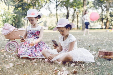 little twins using mobile phone and making selfie