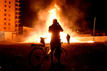 A man on a bicycle takes a picture of a bonfire in the Sandy Row area after it is lit by petrol bombs during the Twelfth of July celebrations held by members of Loyalist Orders in Belfast