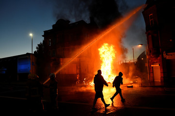 Revellers run past bonfire that firefighters are tackling in East Belfast before the Twelfth of July celebrations held by members of Loyalist Orders in Belfast