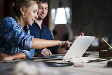 Caucasian woman poiting on computer laptop showing colleague