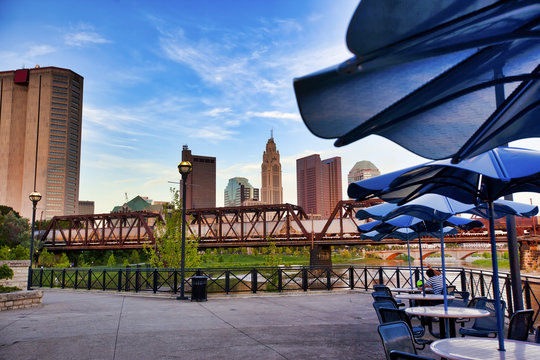 People relax at Northbank Park and enjoy the view of columbus, Ohio and a passing train