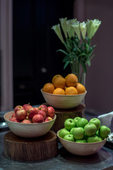 Fruit set : Green and Red apple in bowl with orange on wooden plate and rustic bouquet of flowers in a vase for decoration fruit set in party event.