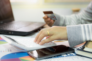 Businesswoman using calculator and holding credit card.