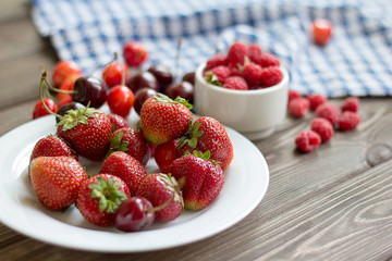 Strawberries, raspberries, cherries in a plate on a wooden table.