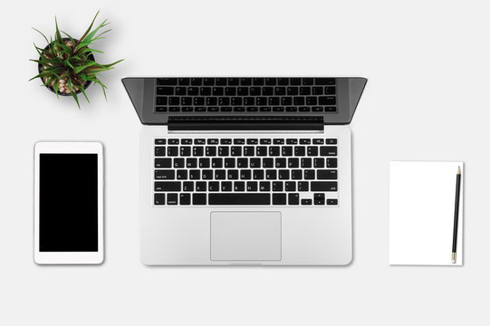 Modern workplace with notebook, smartphone, blank paper, pencil and little tree copy space on gray background. Top view. Flat lay style.