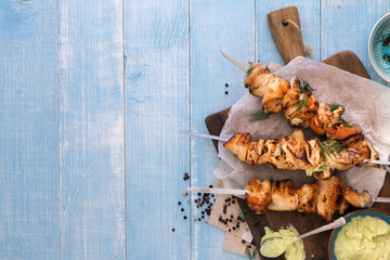 Chicken breast skewers with avocado sauce on blue wooden table