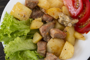 Potatoes with meat and vegetables on a white plate. Tasty and hearty dish.