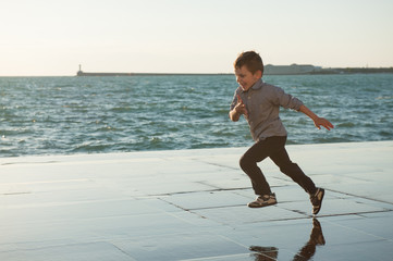 happy little kid running along the sea coast in the city