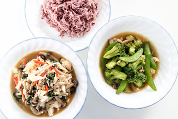 homemade stir-fried vegetable combination and stir-fried crab and mushroom combination with cooked brown rice on white background