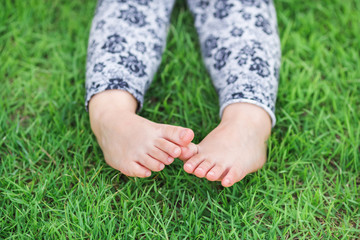 Small feet of a kid on the green grass,Exploring and discovering nature environment and outdoor activity like play, touch and see the real things is the best learning method for children.