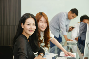 Asian Business women smiling in meeting room