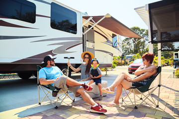 Fotorolgordijn Kamperen Mother,father,son and grandmother sitting near camping trailer,smiling.Woman,men,kid relaxing on chairs near car.Family spending time together on vacation near sea or ocean in modern rv park