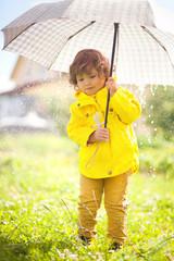 Adorable little girl eith umbrella. Rainy autumn day