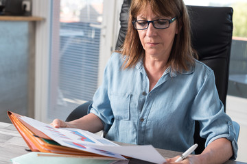 Mature businesswoman checking documents