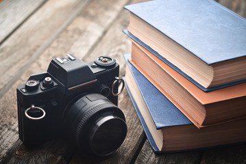 Vintage film camera and many books on a wooden table. The process of learning photography.