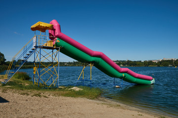 Rubber inflatable hill on the lake shore against the blue sky. Sunny summer day. Water attraction.