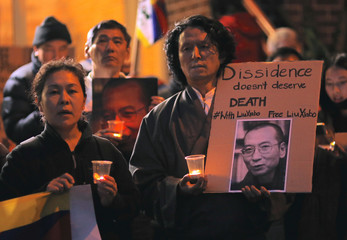 Members of the Australian Tibetan community stand together as they hold placards during a candlelight vigil for the Chinese Nobel Peace Prize-winning dissident Liu Xiaobo outside the Chinese consulate in Sydney