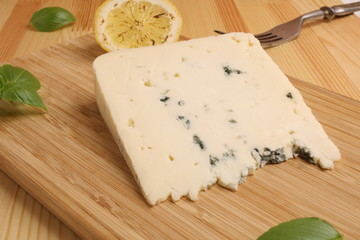 blue Cheese on a wooden board with basil