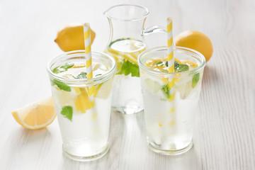 Fresh lemon water drink / Fresh lemon cold water drink lemonade with mint in two glass