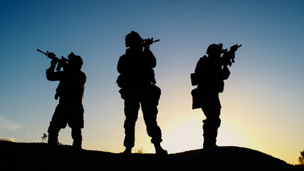 Squad of Three Fully Equipped and Armed Soldiers Standing in Desert Environment in Sunset Light.