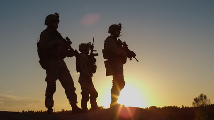 Squad of Three Fully Equipped and Armed Soldiers Standing on Hill in Desert Environment in Sunset Light. Wall mural