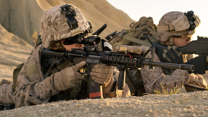 View on Soldiers Lie Down on the Hill, Aim through the Assault Rifle Scope in Desert Environment.